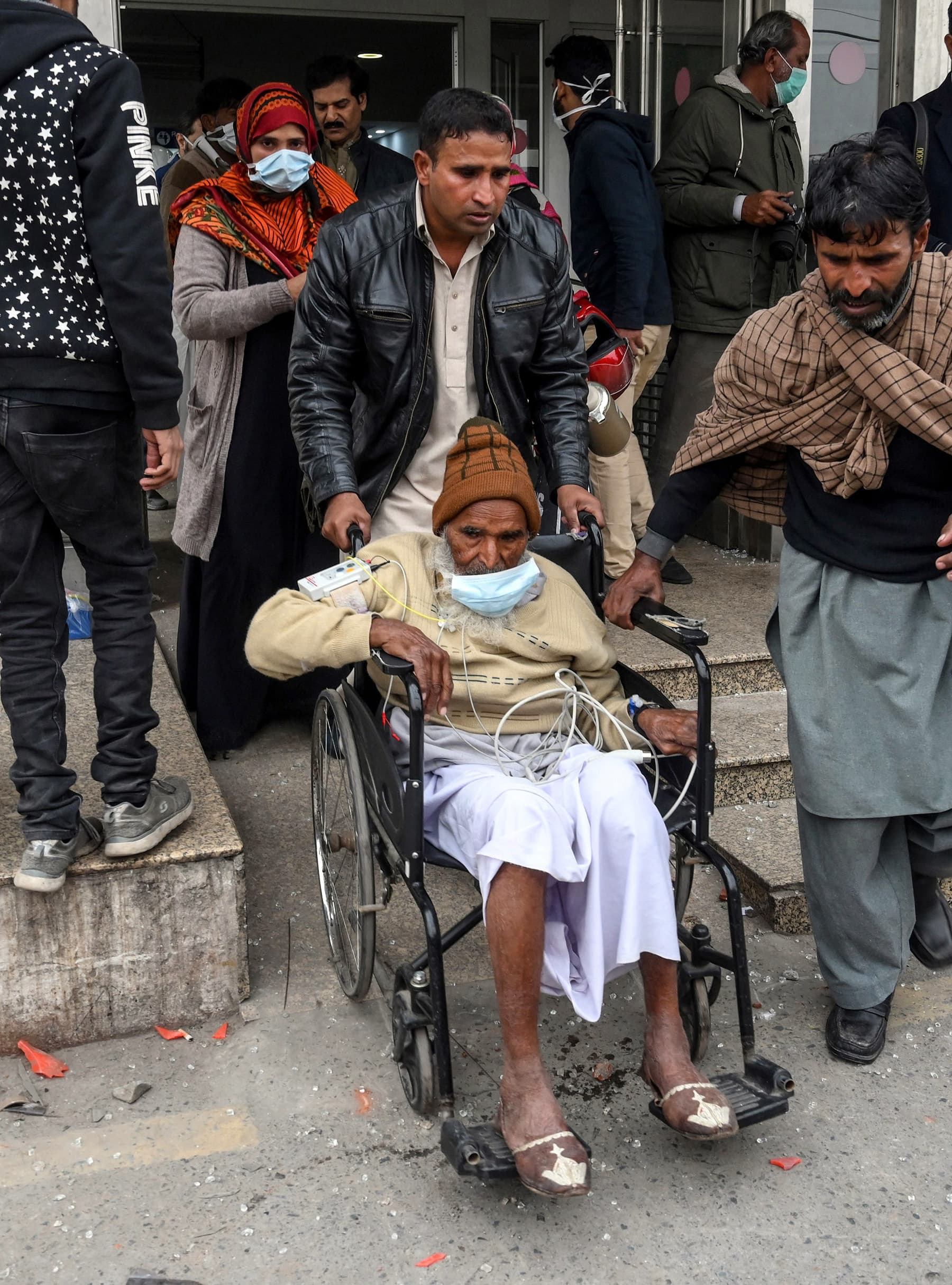People help patients as they come out from the cardiac hospital following an attack by lawyers in the premises in Lahore. — AFP