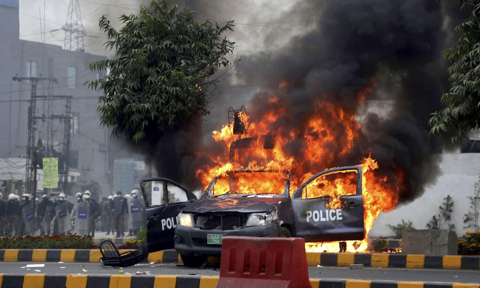 مشتعل افراد نے ایک پولیس موبائل کو بھی آگ لگادی — فوٹو: اے پی