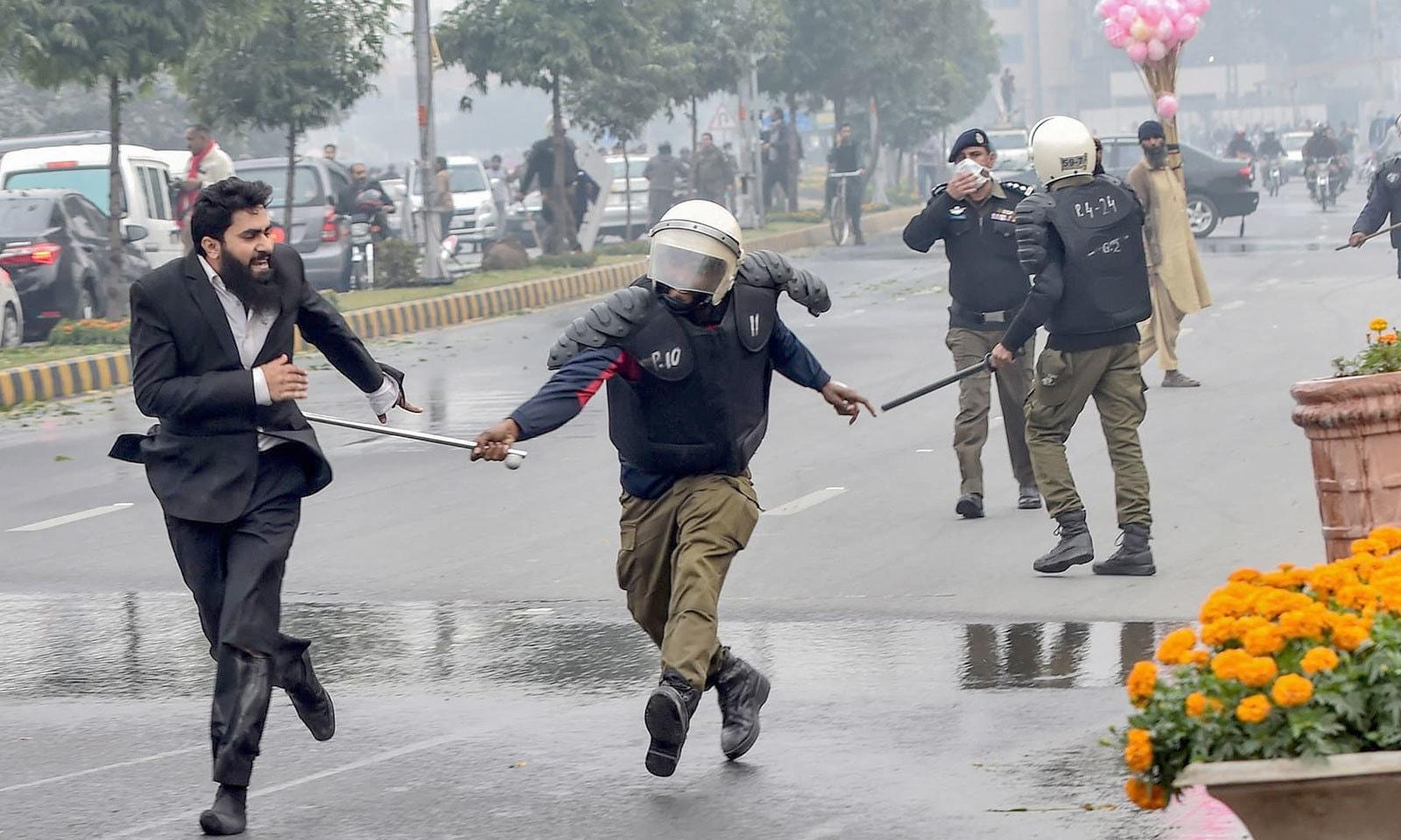پولیس نے مشتعل وکلا کو منتشر کرنے کے لیے آنسو گیس کا استعمال کیا اور لاٹھی چارج بھی کیا — فوٹو: اے ایف پی