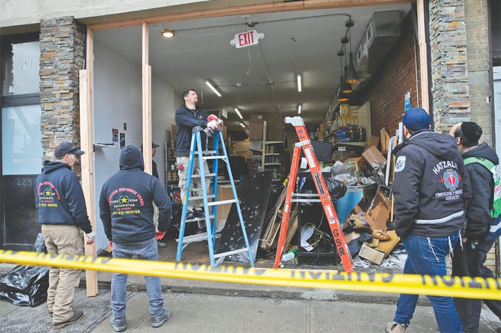 JERSEY CITY: People working at the site of the attack on Wednesday.—AP