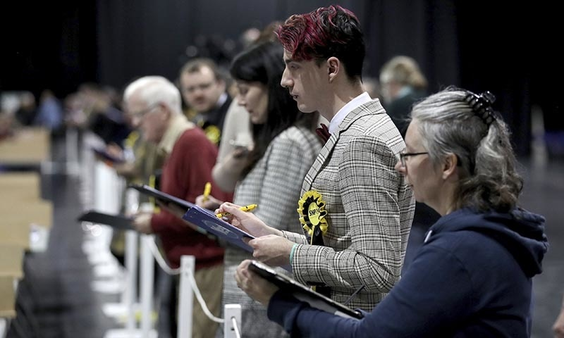Election agents watch as ballot papers are counted at the SEC Centre in Glasgow, Scotland on Thursday. — PA via AP