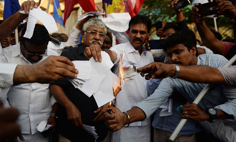 Demonstrators burn a copy of the Citizenship Amendment Bill during a demonstration in Chennai on Dec 12. — AFP.