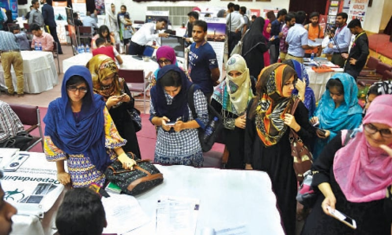 Girls share contact details at a career fair in Lahore. An economic growth rate of over 6.6pc is needed to accommodate 1.3 million new job seekers annually, State Bank of Pakistan estimates.—File photo