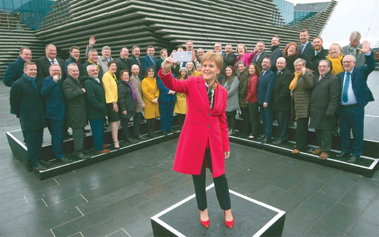 DUNDEE: Scottish National Party leader and Scotland's First Minister Nicola Sturgeon poses with SNP's newly elected MPs during a photo call outside the V & A Museum on Saturday.—AFP