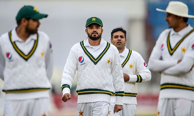 Pakistan's captain Azhar Ali (C) walks back to the pavilion along with teammates after the game has stopped due to bad light conditions during the second day of the first Test cricket match between Pakistan and Sri Lanka at the Rawalpindi Cricket Stadium in Rawalpindi on December 12, 2019. — AFP/File