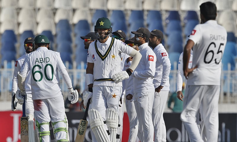 Shan Masood (C) reacts while Sri Lankan players celebrate his dismissal during the fifth day of the first cricket test match between Pakistan and Sri Lanka, in Rawalpindi on Sunday, December 15, 2019. — AP