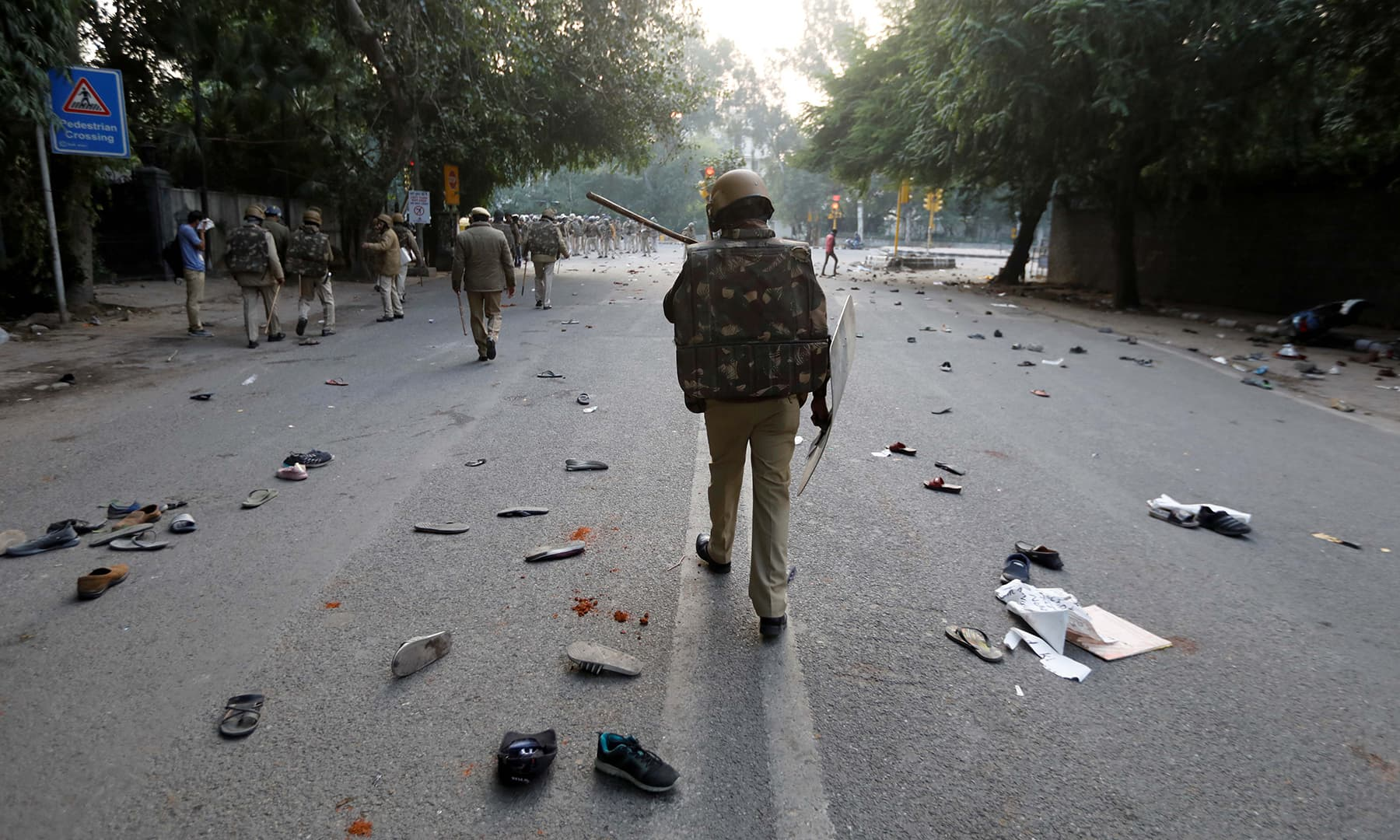 The shoes of demonstrators are seen scattered along the road as police patrol after a protest against a new citizenship law in New Delhi, India on Sunday. — Reuters