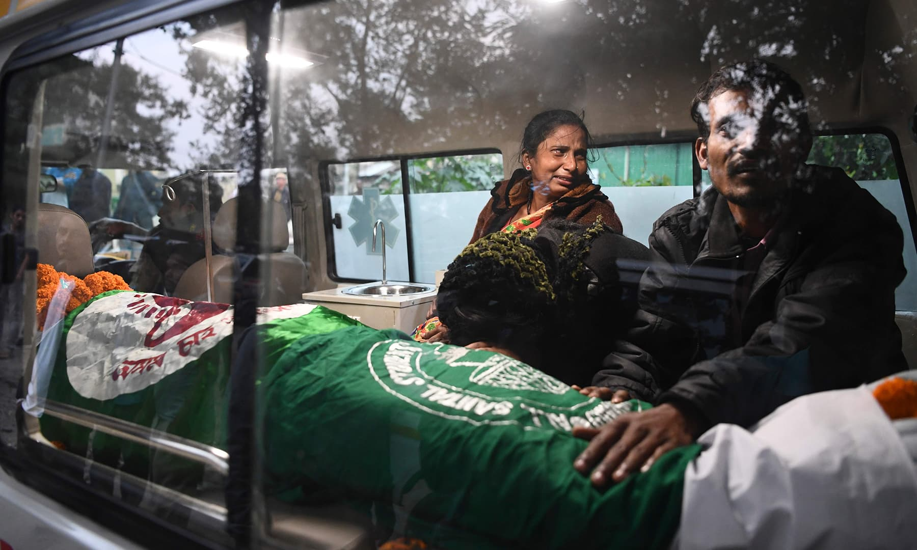 Relatives mourn inside an ambulance next to the dead body of Ishwor Nayak, 25, who was killed after police fired during a protest against the government's citizenship bill. — AFP