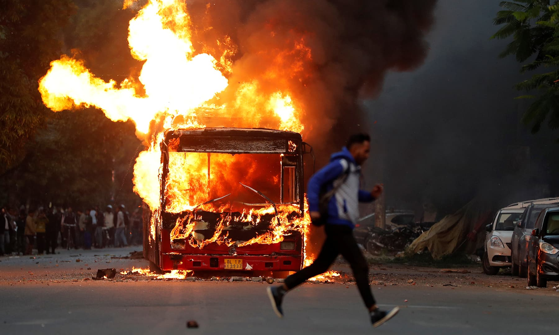 A man runs past a burning bus that was set on fire by demonstrators during a protest against a new citizenship law in New Delhi, India on Sunday. — Reuters
