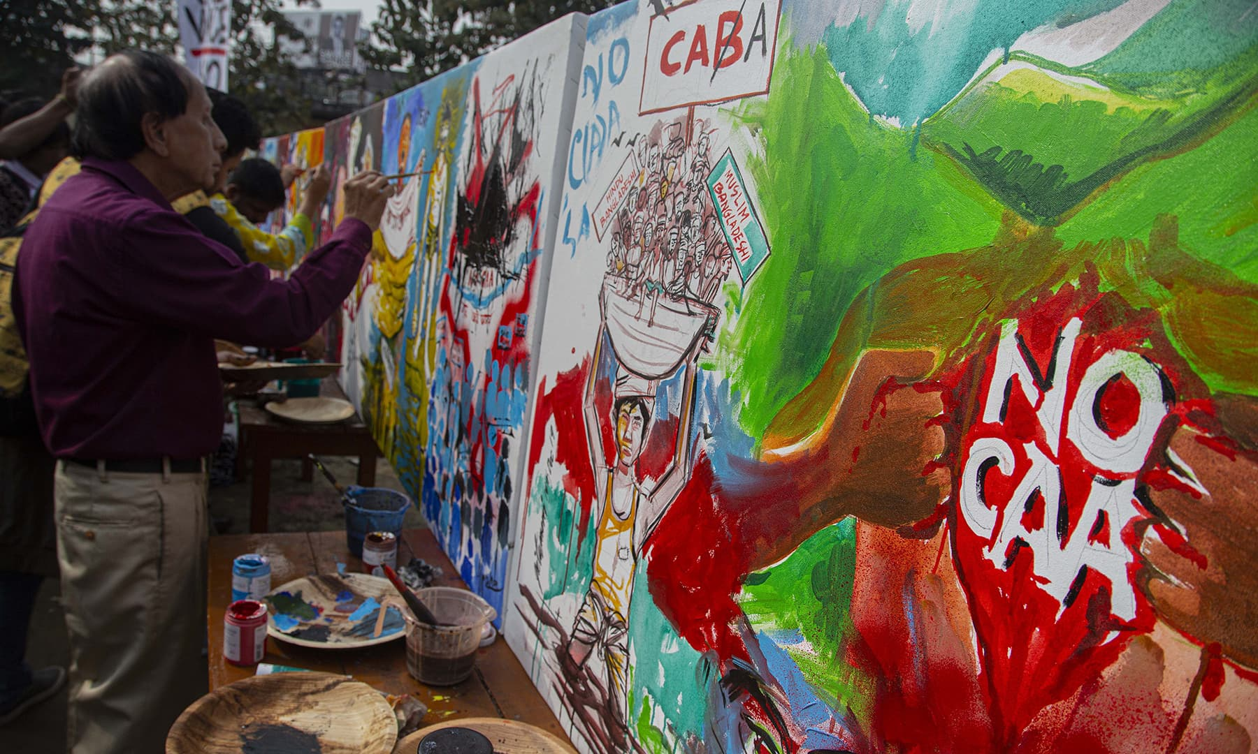 Indian artists paint to protest against the Citizenship Amendment Act in Gauhati, India on Sunday. — AP