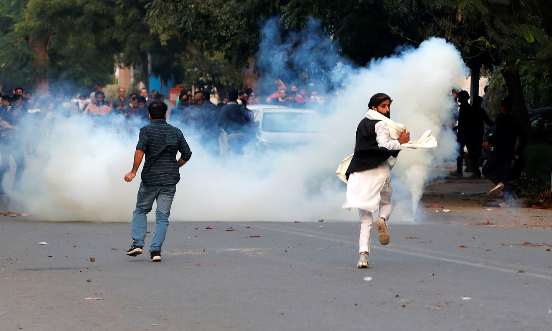 Demonstrators run for cover as smoke billows from a tear gas shell fired during a protest against a new citizenship law in New Delhi, India on Sunday. — Reuters