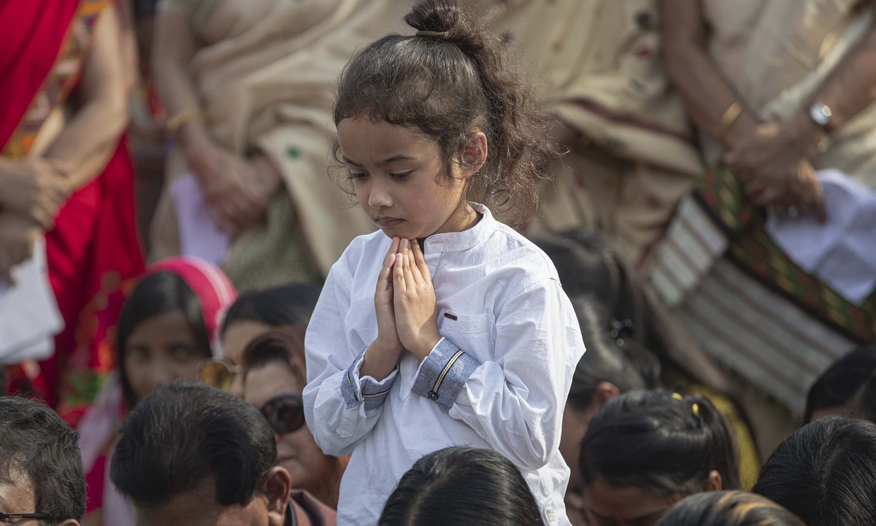 An Indian child prays during a condolence meeting for those killed in protests against the Citizenship Amendment Act in Gauhati, India on Sunday. — AP