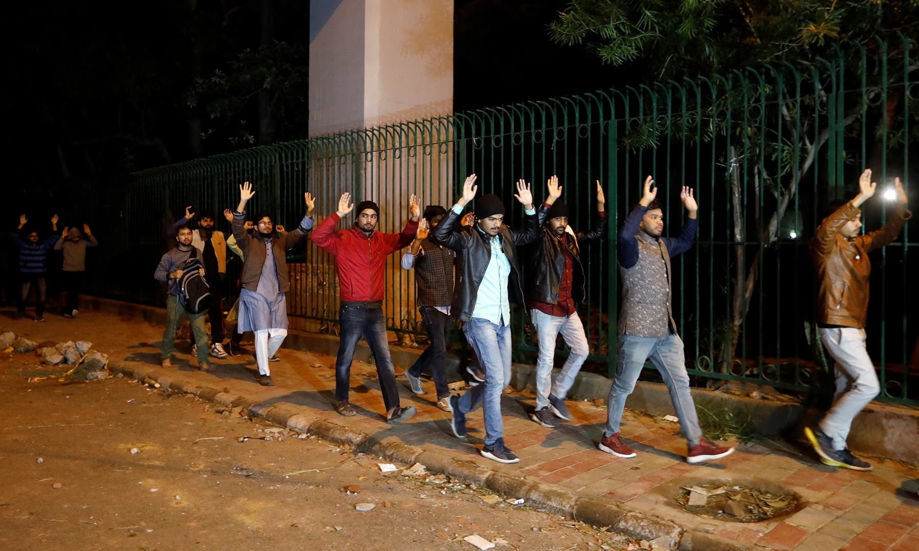 Students raising their hands leave the Jamia Milia University following a protest against a new citizenship law in New Delhi, India on Sunday. — Reuters
