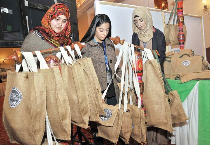 Women purchase jute bags from a stall during the conference on Monday. — APP