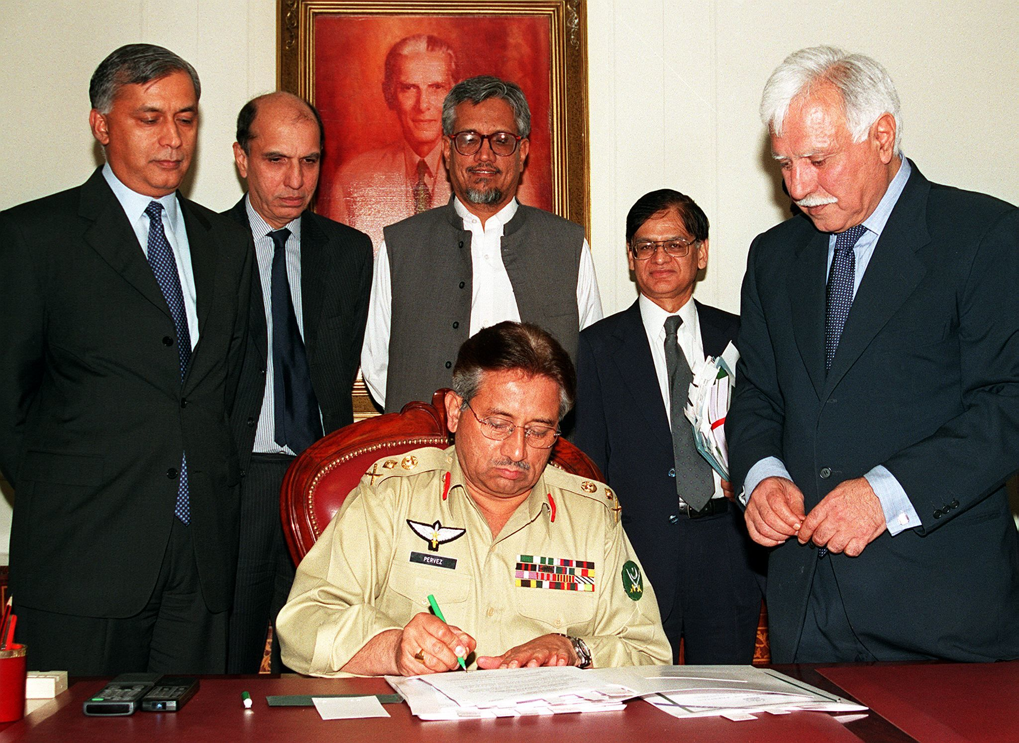 Chief Executive General Pervez Musharraf signs the national budget for the year 2001-02 in Islamabad, June 18, 2001. Finance Minister Shaukat Aziz (L) informed the cabinet that the major thrust of the new budget is on reviving investor-confidence and fostering growth in agricultural and industrial sectors to make the economy stand on its own feet. Others are unidentified finance ministry officials. — AFP