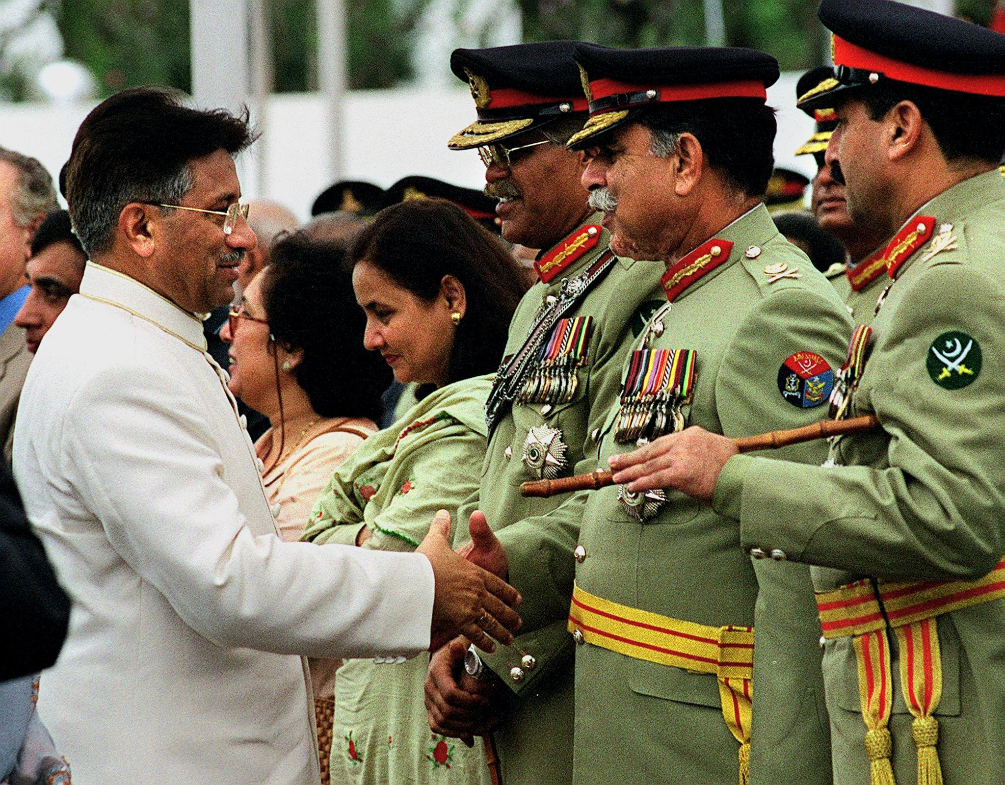 President General Pervez Musharraf (L) shakes hand with top military official, General Mehmood (2nd R), the chief of Inter-Services Intelligence (ISI), after a flag hoisting ceremony to mark the country's 54th Independence Day in Islamabad, August 14, 2001. — AFP