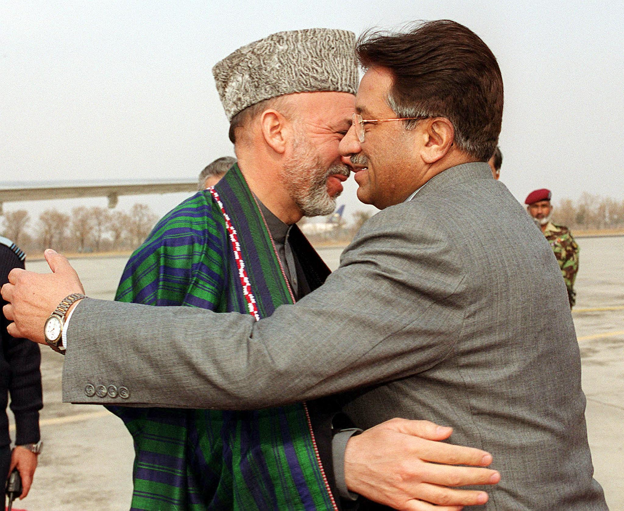 Musharraf hugs Afghan interim leader Hamid Karzai at Chaklala airbase in Rawalpindi, February 8, 2002. Karzai arrived for his first visit to Pakistan since he took office in December 2001. — AFP