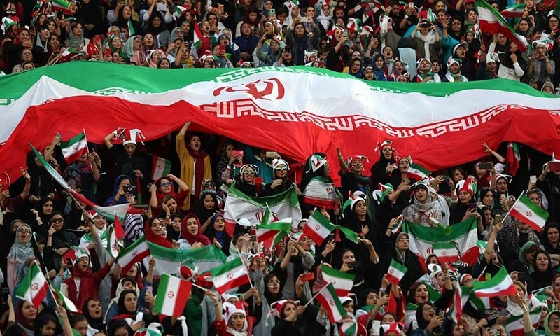 Iranian women cheer as they hold a huge Iranian flag during a soccer match between their national team and Cambodia in the 2022 World Cup qualifier at the Azadi (Freedom) Stadium in Tehran, Iran on October 10. — AP via Al-Jazeera