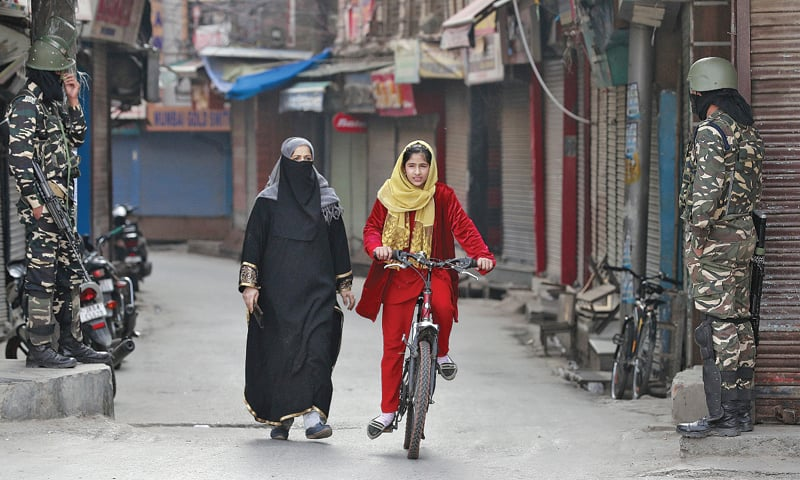 SRINAGAR: A Kashmiri girl rides her bike past a woman and Indian security force personnel standing guard in front closed shops in a street.—Reuters