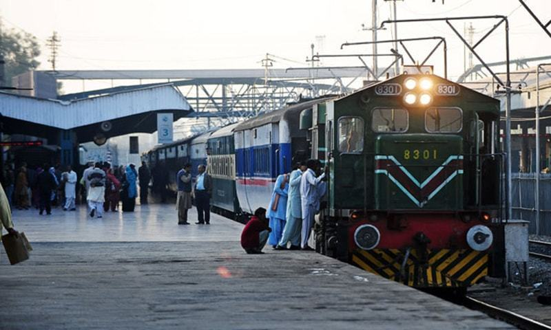 Passengers board a train at a station. — AFP/File