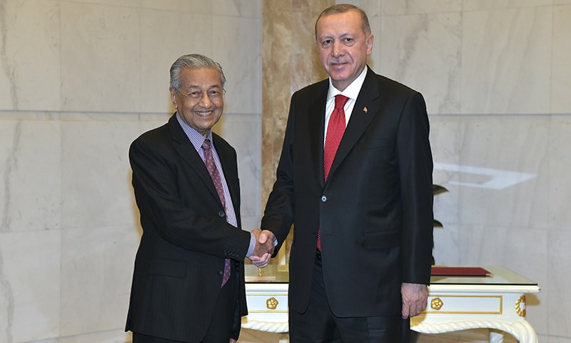 Turkey's President Recep Tayyip Erdogan, right, shakes hands with Malaysia's Prime Minister Mahathir Mohamad before their meeting in  Malaysia on Dec 18. — AP