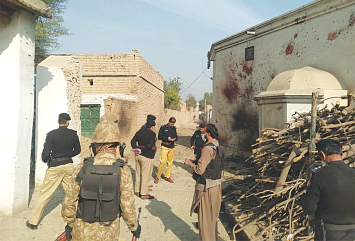 LAKKI MARWAT: Personnel of law enforcement agencies and bomb disposal unit inspect the explosion site.—Dawn