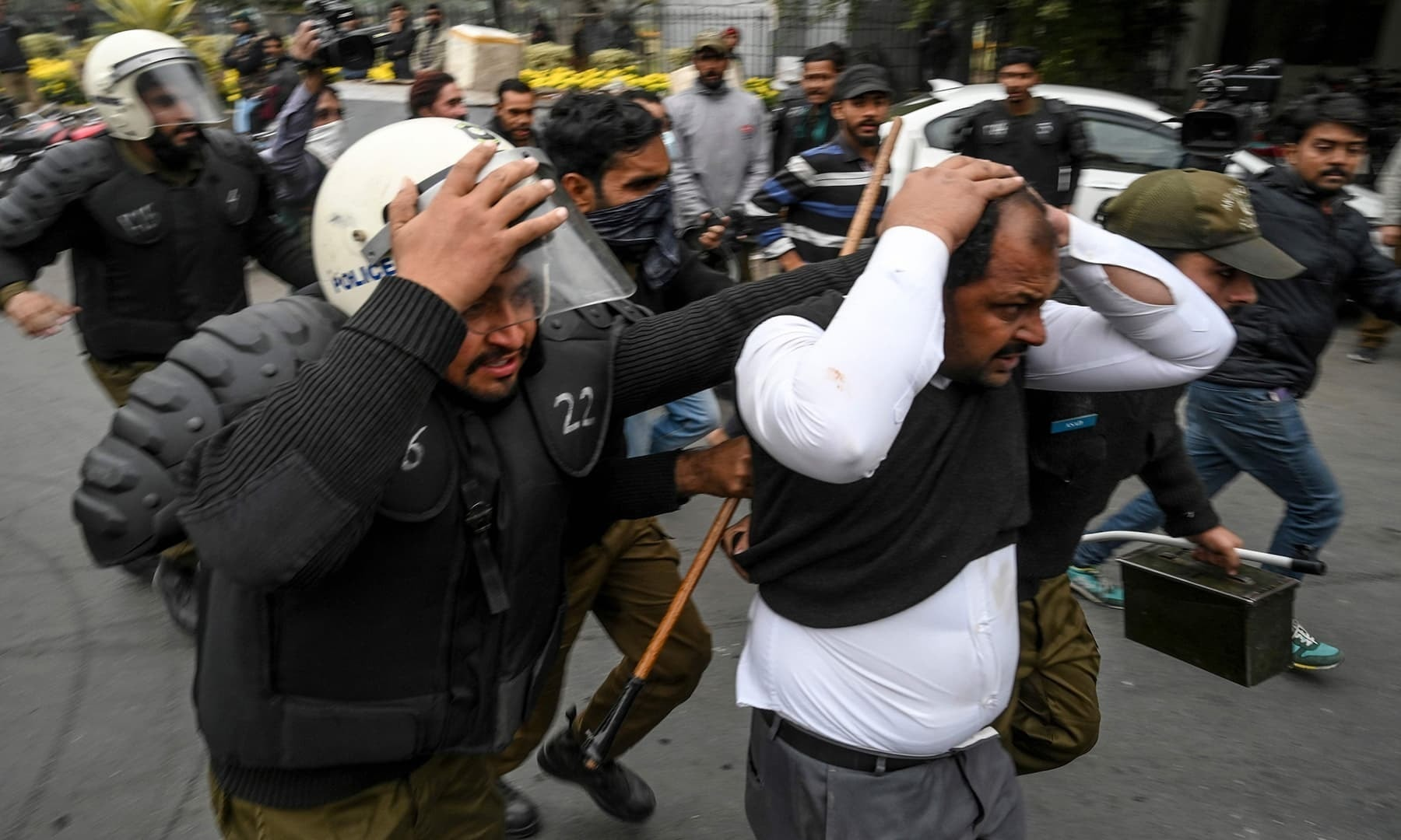 In this file photo, policemen detain a lawyer following a clash between lawyers and doctors in Lahore on December 11. — AFP