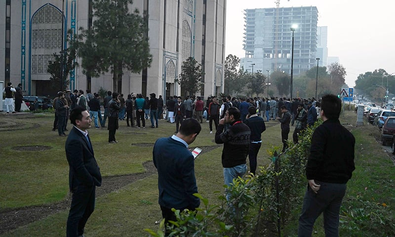 People gather outside buildings after an earthquake in Islamabad on Friday. — AFP