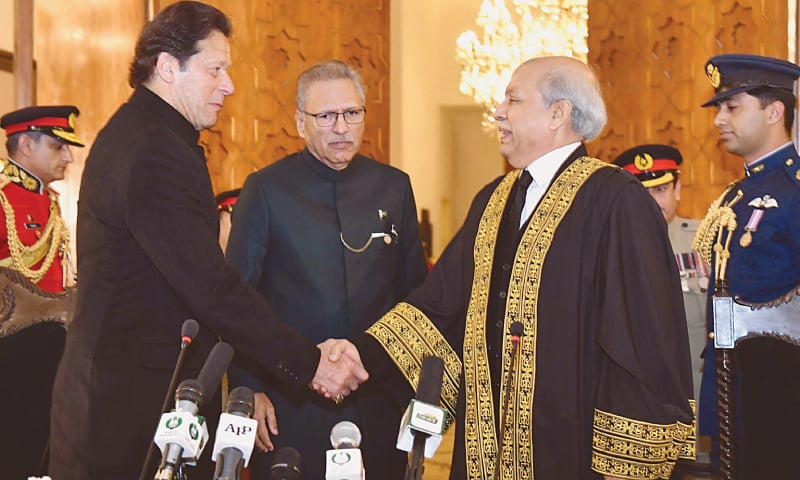 ISLAMABAD: Prime Minister Imran Khan shaking hands with new Chief Justice of Pakistan Gulzar Ahmed after the latter took oath of his office on Saturday. President Dr Arif Alvi is also seen.—White Star