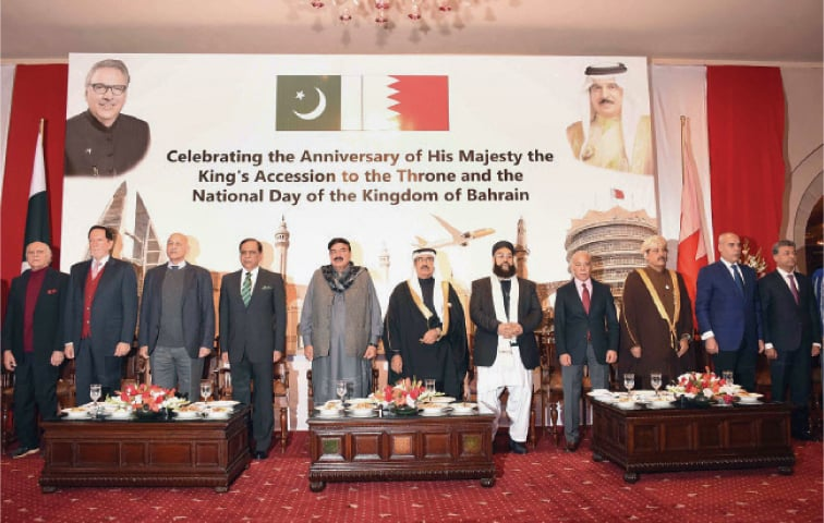 Federal Minister Sheikh Rashid Ahmed, Ambassador Mohamed Ebrahim Mohamed and other guests listen to the national anthem at Bahrain's National Day celebrations in Islamabad.