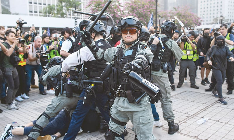 HONG KONG: A police officer holds aloft his baton as his colleagues detain a man during the rally.—AFP