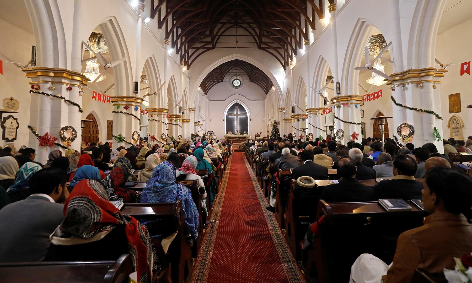 People attend a Christmas Day service at the St. John's Cathedral in Peshawar. — Reuters