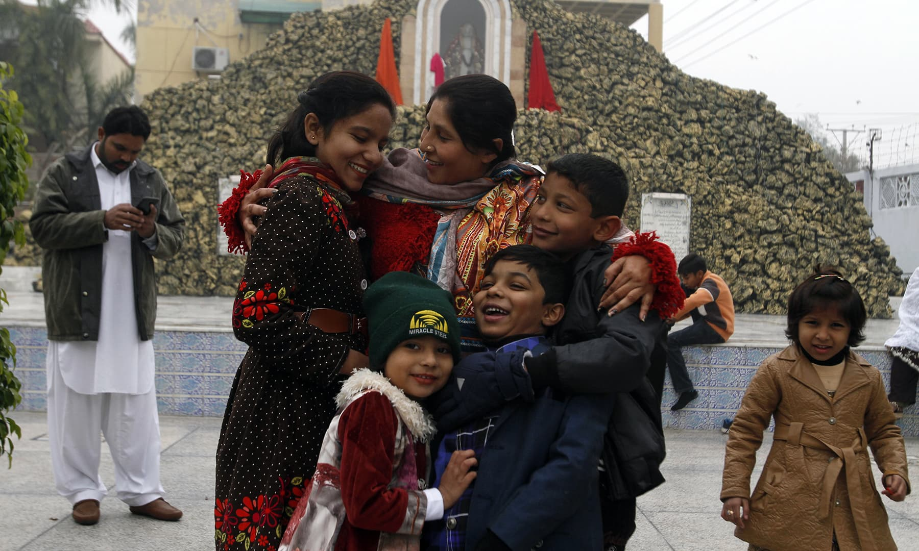 A Christian family greet each other after attending Christmas Mass at a church in Multan on Wednesday. — AP