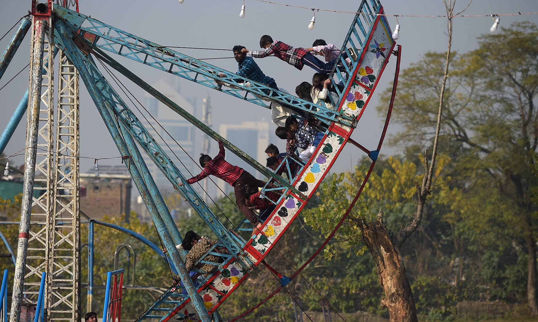 Children ride on a swing on Christmas Day in Islamabad. — AFP