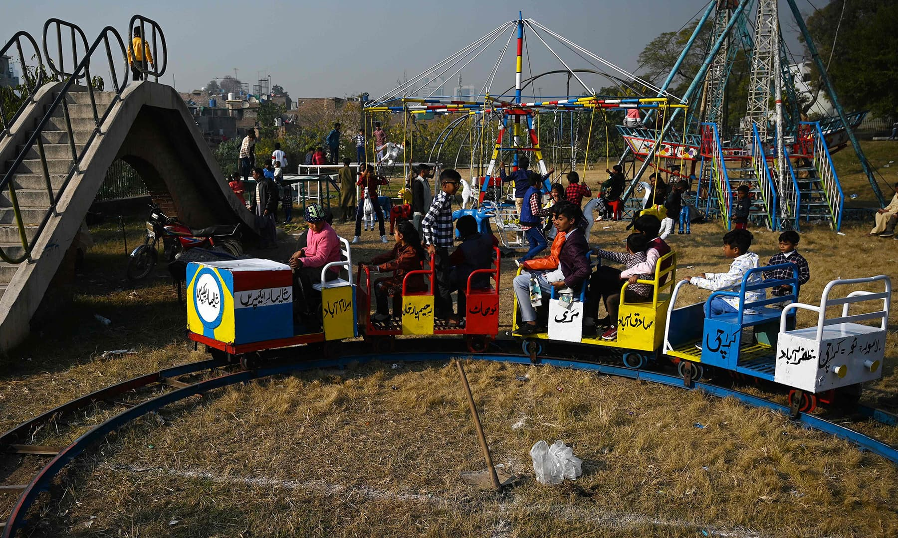 Children ride on a toy train on Christmas Day in Islamabad on December 25. — AFP