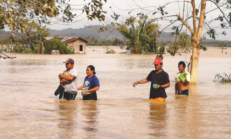 Ormoc City (Leyte province, Philippines): Residents wade through a flooded highway after heavy rains spawned  by the typhoon.—AFP