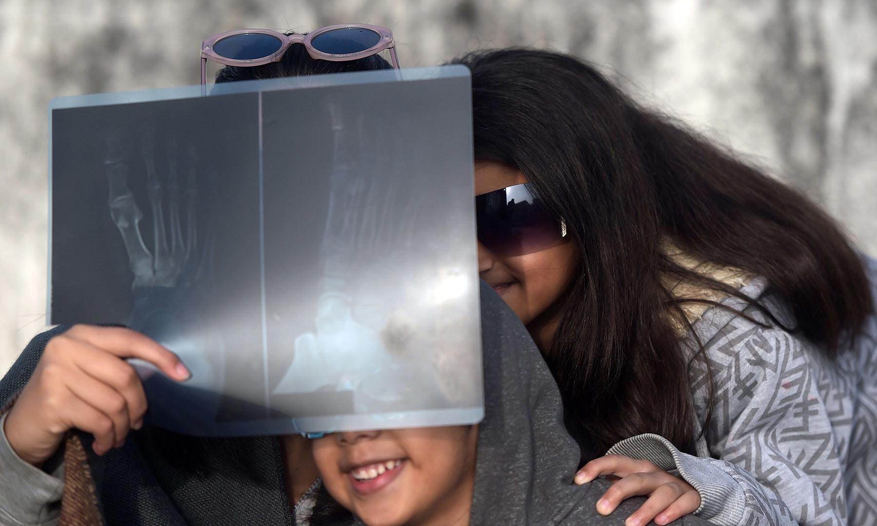 """Children watch the solar eclipse through a foot X-ray as the moon covers the sun in a rare """"ring of fire"""" solar eclipse as seen from Islamabad on December 26. — AFP"""