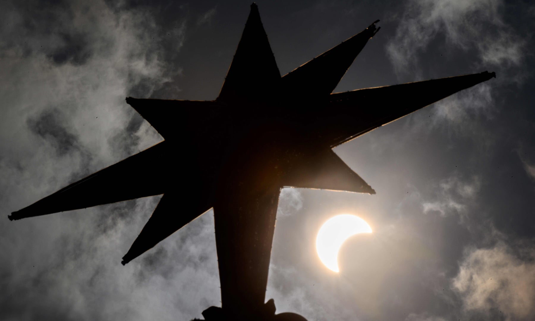 """The moon begins to cover the sun in a rare """"ring of fire"""" solar eclipse as seen behind a Christmas tree star in Bangkok on December 26. — AFP"""