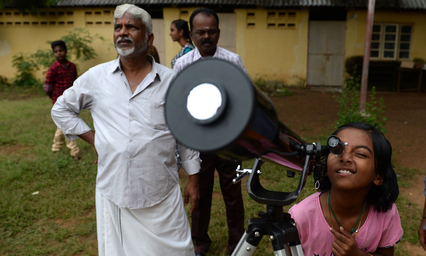 """A girl uses a telescope to watch the moon covering the sun in a rare """"ring of fire"""" solar eclipse as seen from the south Indian city of Dindigul in Tamil Nadu state on December 26. — AFP"""