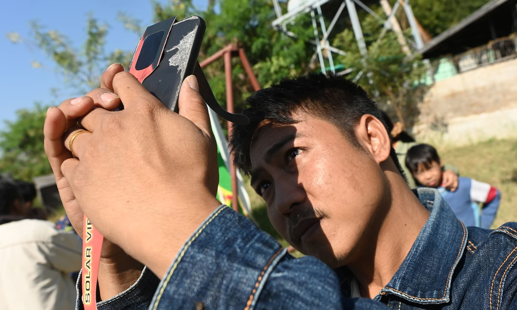 """A man uses his mobile phone to take a picture of a rare """"ring of fire"""" solar eclipse in Wan Twin in central Myanmar on December 26. — AFP"""