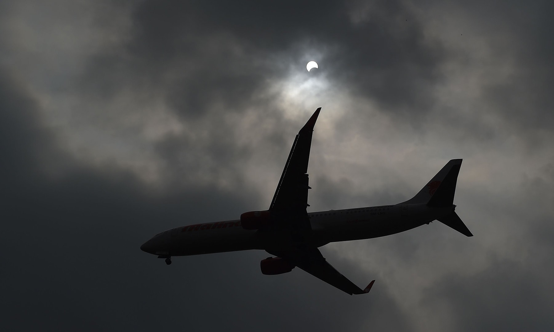 """An airplane flies past as the moon moves in front of the sun in a rare """"ring of fire"""" solar eclipse as seen from Hanoi on December 26. — AFP"""