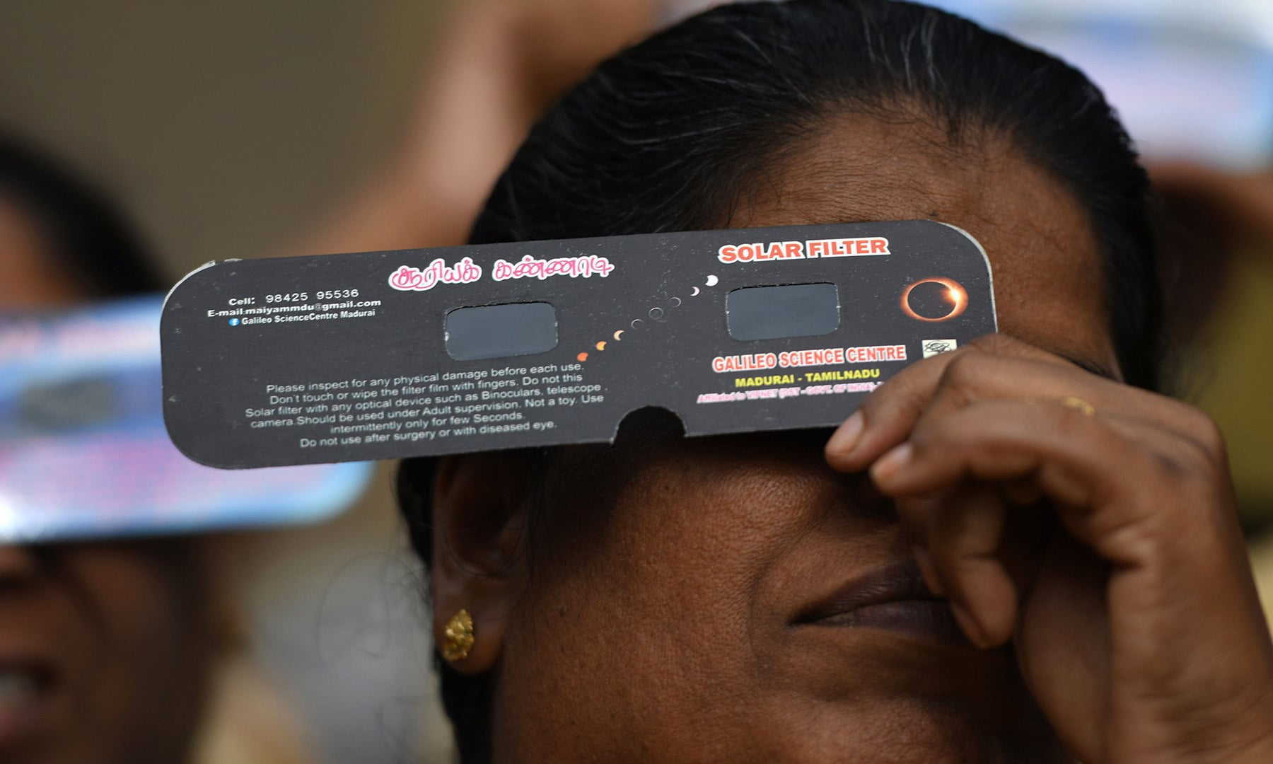 """A woman uses solar filter glasses to watch the moon covering the sun in a rare """"ring of fire"""" solar eclipse as seen from the south Indian city of Dindigul in Tamil Nadu state on December 26. — AFP"""