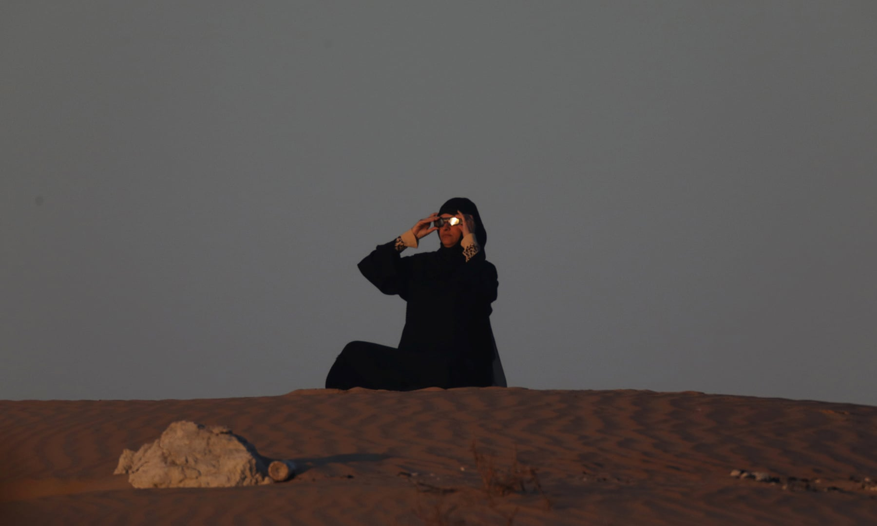 An Emirati woman views an annular solar eclipse in Madinat Zayed in the Al Dhafra region of Abu Dhabi, United Arab Emirates on December 26. — Reuters