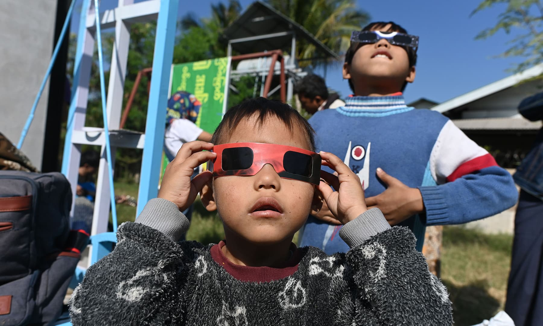 """A child uses eclipse glasses to watch a rare """"ring of fire"""" solar eclipse in Wan Twin in central Myanmar on December 26. — AFP"""