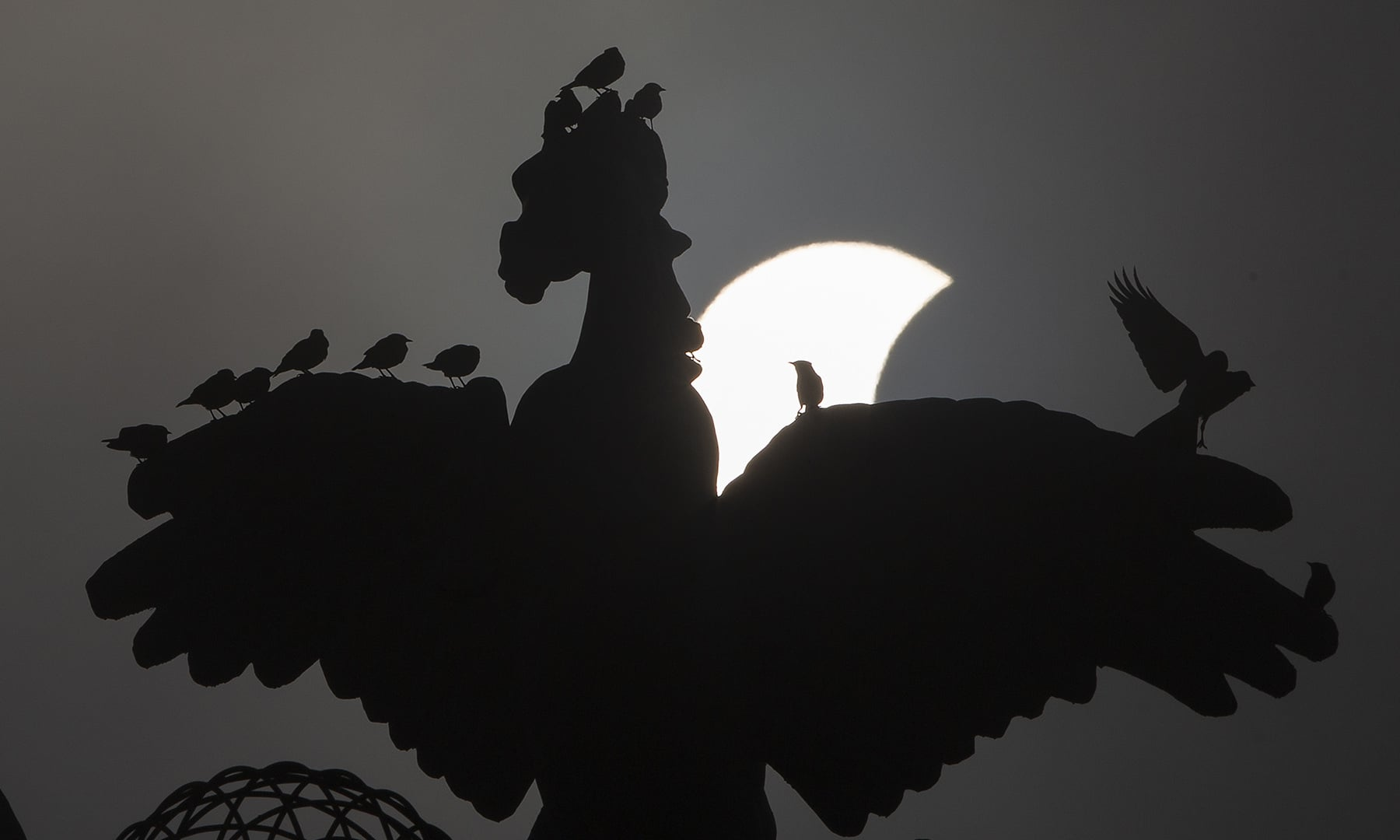A partial solar eclipse moves behind a statue in Islamabad on Thursday. — AP