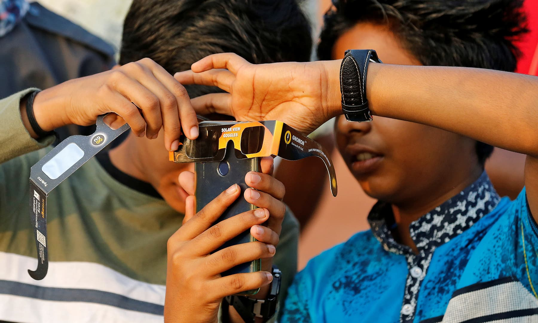 Boys use their mobile phone and solar viewers to take photographs of annular solar eclipse in Cheruvathur town in the southern state of Kerala, India on December 26. — Reuters