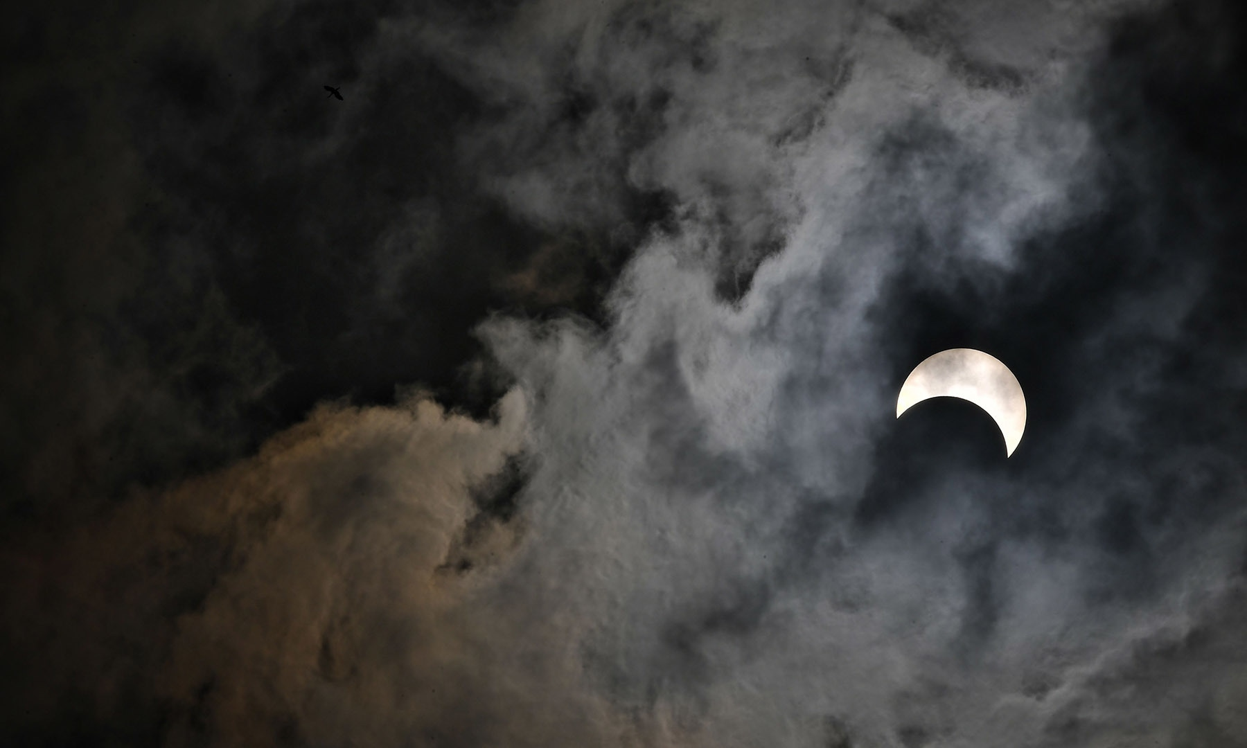 """The moon moves in front of the sun in a rare """"ring of fire"""" solar eclipse in Bangkok on December 26, 2019. (Photo by Lillian SUWANRUMPHA / AFP) — AFP or licensors"""
