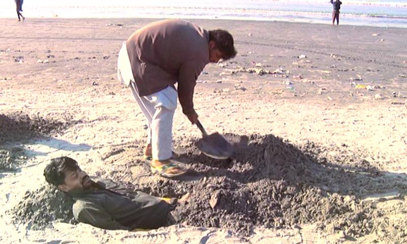 کچھ افراد گرہن کے دوران ریت میں دبنے کو بیماری سے نجات کا ذریعہ سمجھتے ہیںـــتصویر ڈان نیوز