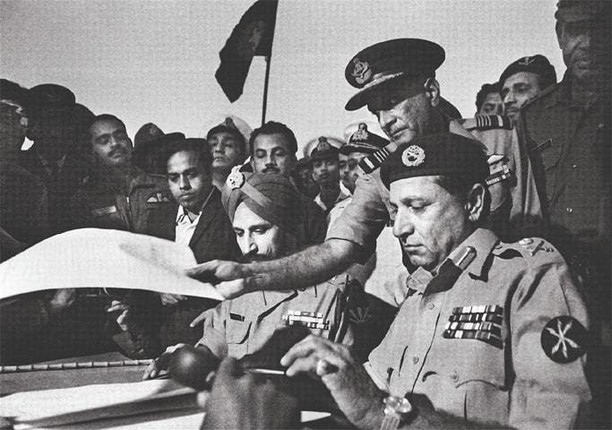 Gen Niazi (right) signs the Treaty of Surrender on December 16, 1971. — Raghu Rai