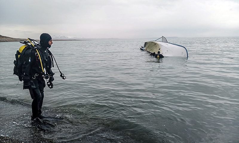 A handout image made available by the Demiroren news Agency shows a rescue diver standing on the shores of Lake Van after a boat carrying refugees and migrants sank in eastern Turkey on Thursday. — AFP